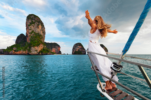 Joyful young woman portrait. Happy girl stand on deck of sailing yacht, have fun discovering islands in tropical sea on summer coastal cruise. Travel adventure, yachting with kids on family vacation.