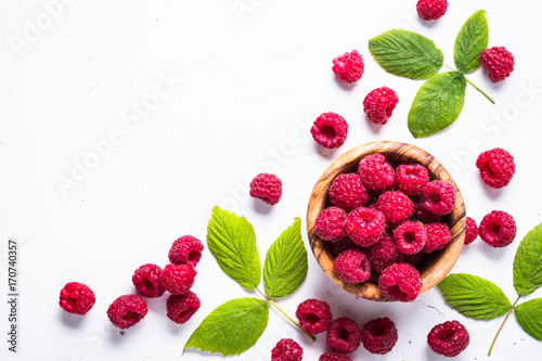 Fresh raspberries in wooden bowl on white table. Top view.