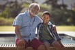 Smiling grandfather and grandson sitting together on bench
