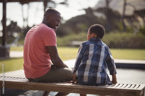 Father talking to son near pool side