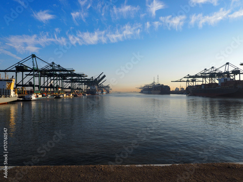 Montage in der Fensternische Antwerpen Antwerp, Belgium - March 28 2017: Harbor cranes unloading containers from ships on a sunny morning in the port of Antwerp.