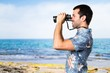Handsome man with flower shirt with binoculars at the beach
