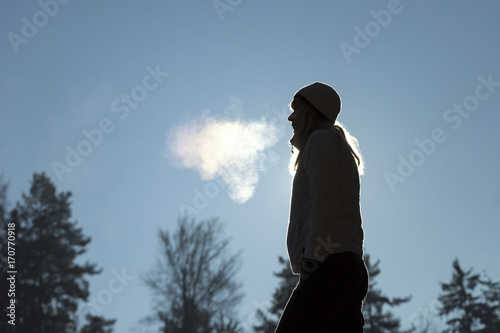 Fototapeta Silhouette of a woman with hat breathing warm air during a cold winter morning. Selective focus used. obraz