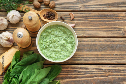 Bowl with tasty spinach sauce on table