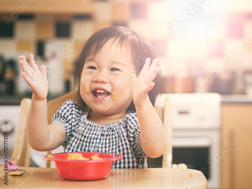 baby girl eating vegetable at home Canvas Print
