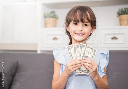 Photo Cute little girl holding money in the living room