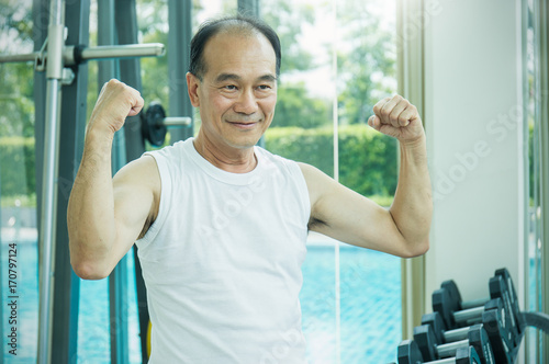 Photo  Asian senior male doing weight training with dumbbells, Happy senior man showing