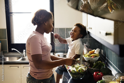 Poster Cuisine Black kid feeding mother with cooking food in the kitchen