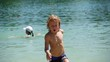 little blond boy playing at the beach