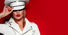 Beautiful Young Fashionable Girl In A White Cap And White Jacket On A Red Background With Red Lips And Nails.Fashion, Beauty, Fashionable Clothes, Headdress, Cap, Military Uniform,red Lipstick.