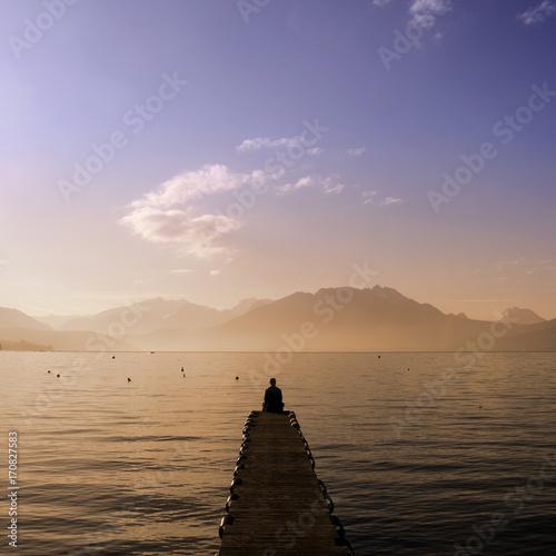 Man sitting on Annecy lake pontoon Wall mural