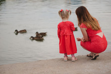 Mother With Daughter Feeding Ducks In Park