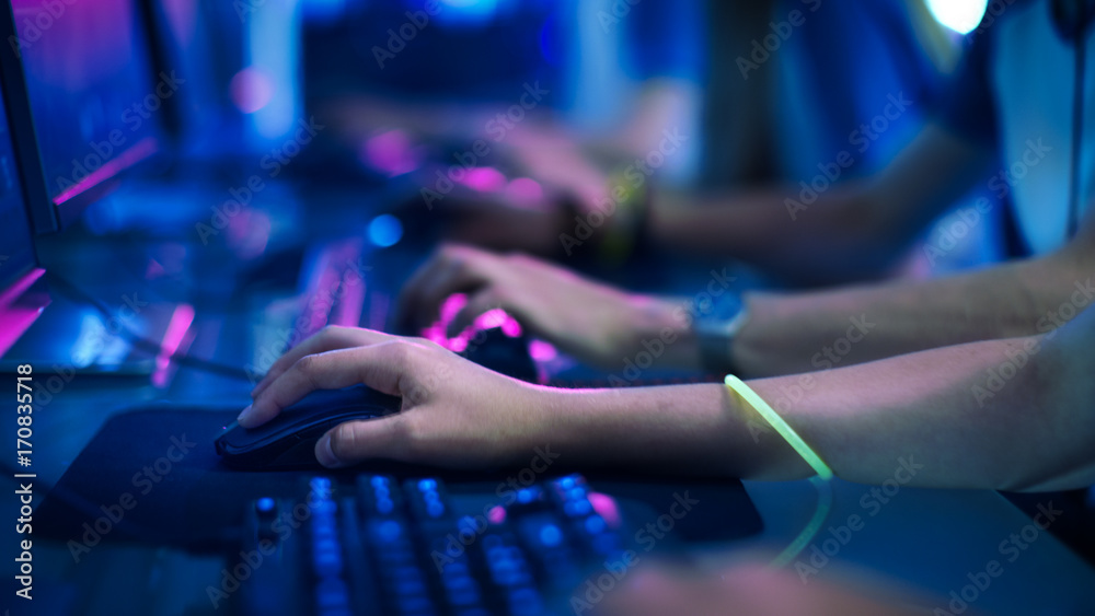 Fototapety, obrazy: Close-up On Row of Gamer's Hands on a KeyBoard.jpgs, Actively Pushing Buttons, Playing MMO Games Online. Background is Lit with Neon Lights.