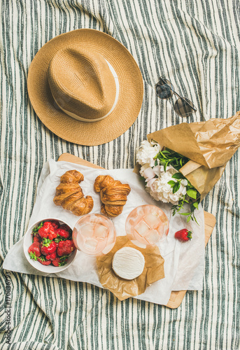 Keuken foto achterwand Picknick French style summer picnic setting. Flat-lay of glasses with rose wine, fresh strawberries, croissants, brie cheese on wooden board, hat, sunglasses, peony flowers, top view. Outdoor gathering concept