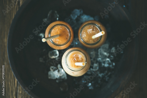 Fototapety, obrazy: Refreshing summer drink. Cold Thai iced tea in glass bottles with milk on plate over dark wooden background, top view. Vegetarian, healthy food concept