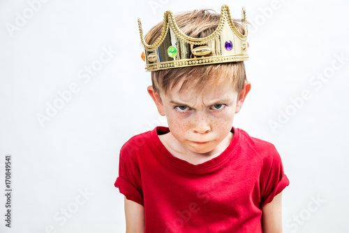 irritated beautiful spoiled boy with dirty look and golden crown