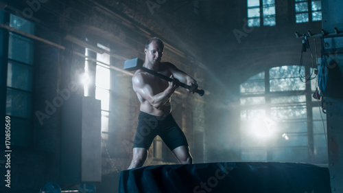 Valokuva  Strong Muscular Man Hits Tire with a Sledgehammer as Part of His Cross Fitness Bodybuilding Gym Training