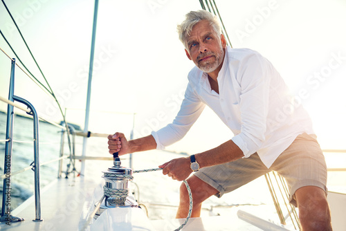 Fotografía  Mature man using a winch while out sailing