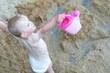 Cute toddler is playing with plastic jug on beach during summer. View from above.
