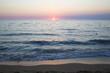 Vista del tramonto dalla spiaggia. Ilmare è calmo e le onde sono poche che si infrangono sulla battigia. Il sole all'orizzonte dona le tinte calde al paesaggio.