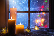 canvas print picture Winter decoration with candles near the snow-covered window