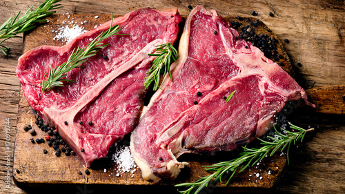 Garden Poster Steakhouse Raw fresh meat t-bone steak and seasoning on wooden background