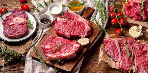 Raw beef meat on a dark wooden board. Wallpaper Mural