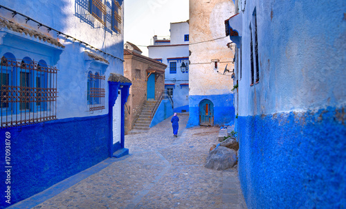 Poster Marokko A Moroccan woman in national clothes is walking down the street of the city