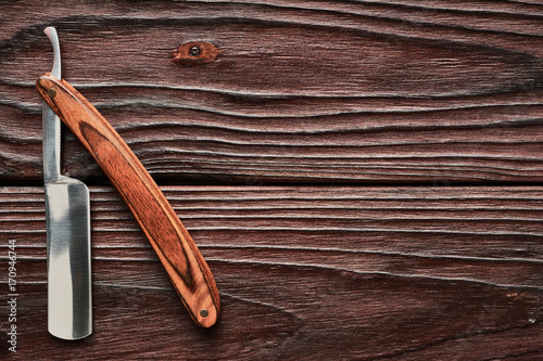 Vintage barber shop straight razor tool on wooden background Plakat