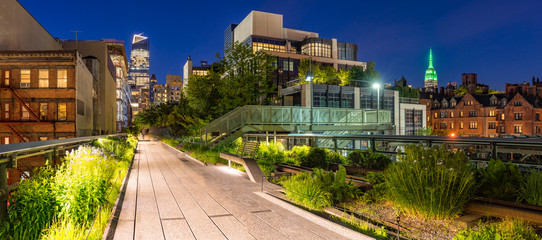 Panoramic view of the High Line promenade at twilight with city lights and illuminated skyscrapers. Chelsea, Manhattan, New York City