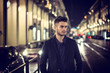 Attractive young man portrait at night with city lights behind him in Turin, Italy
