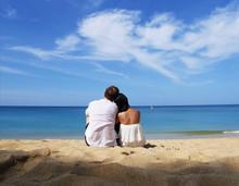 A Happy Couple In White Sittin...