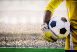 Fototapeta Sport - goalkeeper with a soccer ball in the stadium