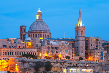 Fototapeta na wymiar Valletta Skyline from Sliema with church of Our Lady of Mount Carmel and St. Paul's Anglican Pro-Cathedral during evening blue hour, Valletta, Capital city of Malta