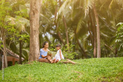 Poster Palmier Nice caring thai woman reading book with her little daughter