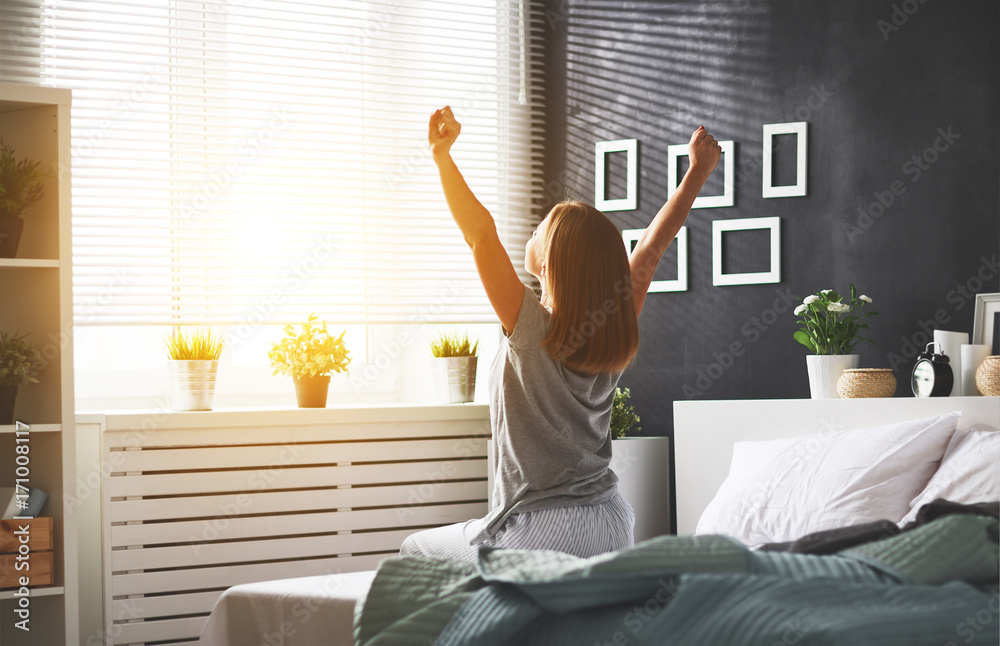 Fototapeta young   woman woke up in the morning in the bedroom by the window with her back