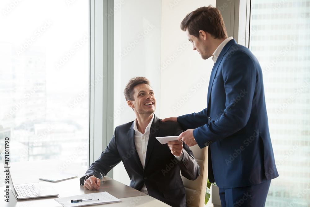 Fototapeta General manager presenting an envelope with premium or bonus cash to male company official. Boss congratulating happy employee with career promotion, thanking for good job and giving financial reward