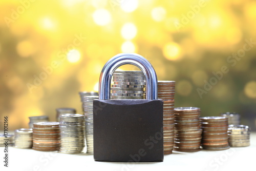 Fototapeta Coin money stack and lock, on gold light background. Saving and financial security concept. obraz