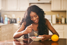 Smiling Young Woman Eating Bre...