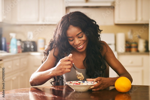 Poster Kruidenierswinkel Smiling young woman eating breakfast at table in kitchen