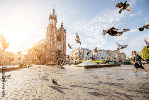 Poster Cracovie View on the central square and famous st. Marys basilica with pigeons flying during the sunrise in Krakow, Poland