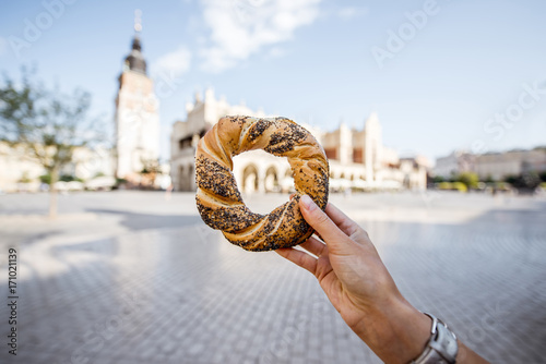 Fototapeta Holding prezel, traditional polish snack on the Market square in Krakow obraz