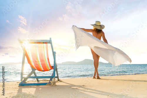 Obraz na plátne Young woman lying on sun lounger near the sea
