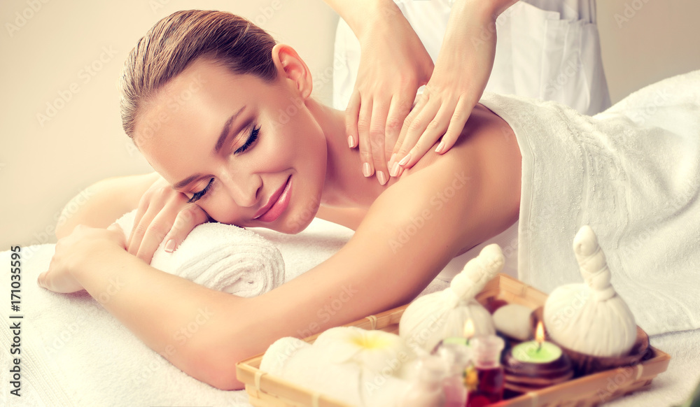 Fototapeta Massage and body care. Spa body massage treatment. Woman having massage in the spa salon for beautiful girl