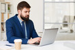 Portrait of modern bearded businessman working with laptop at desk in office