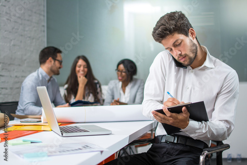 Fototapety, obrazy: Young businessman holding mobile phone between ear and shoulder talking and writing notes to clipboard in modern office, while his business partners having meeting in the background.