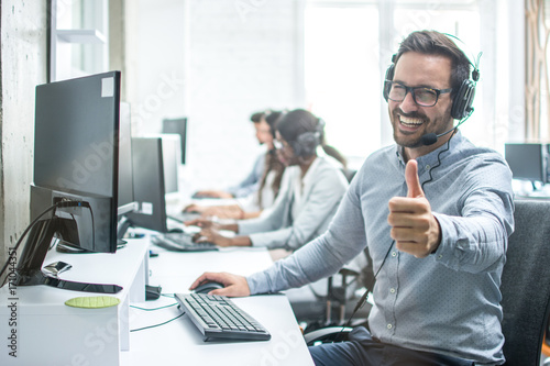 Fotografering Cheerful male customer service operator showing thumbs up in office