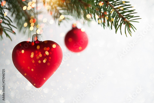 red christmas ornaments heart and ball on the xmas tree on glitter bokeh background