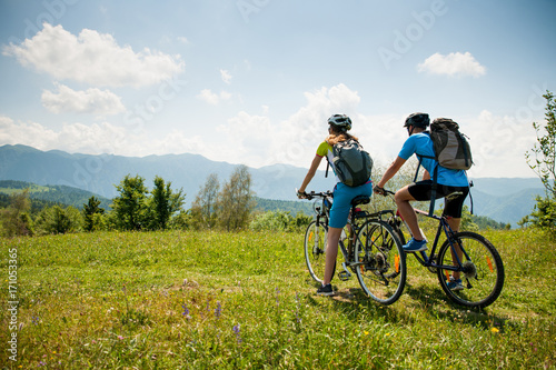 ACTIVE Young couple biking on a forest road in mountain on a spring day