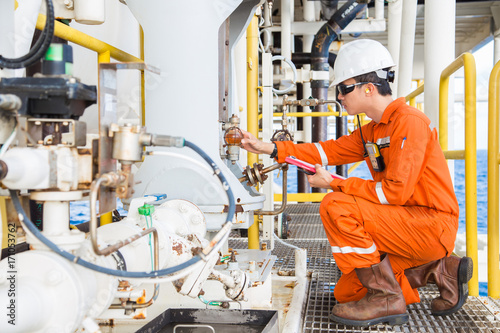 Fotografía Mechanical engineer checking lube oil system of centrifugal pump and electric motor at offshore oil and gas central processing platform, Oil and gas exploration and production in the gulf of Thailand